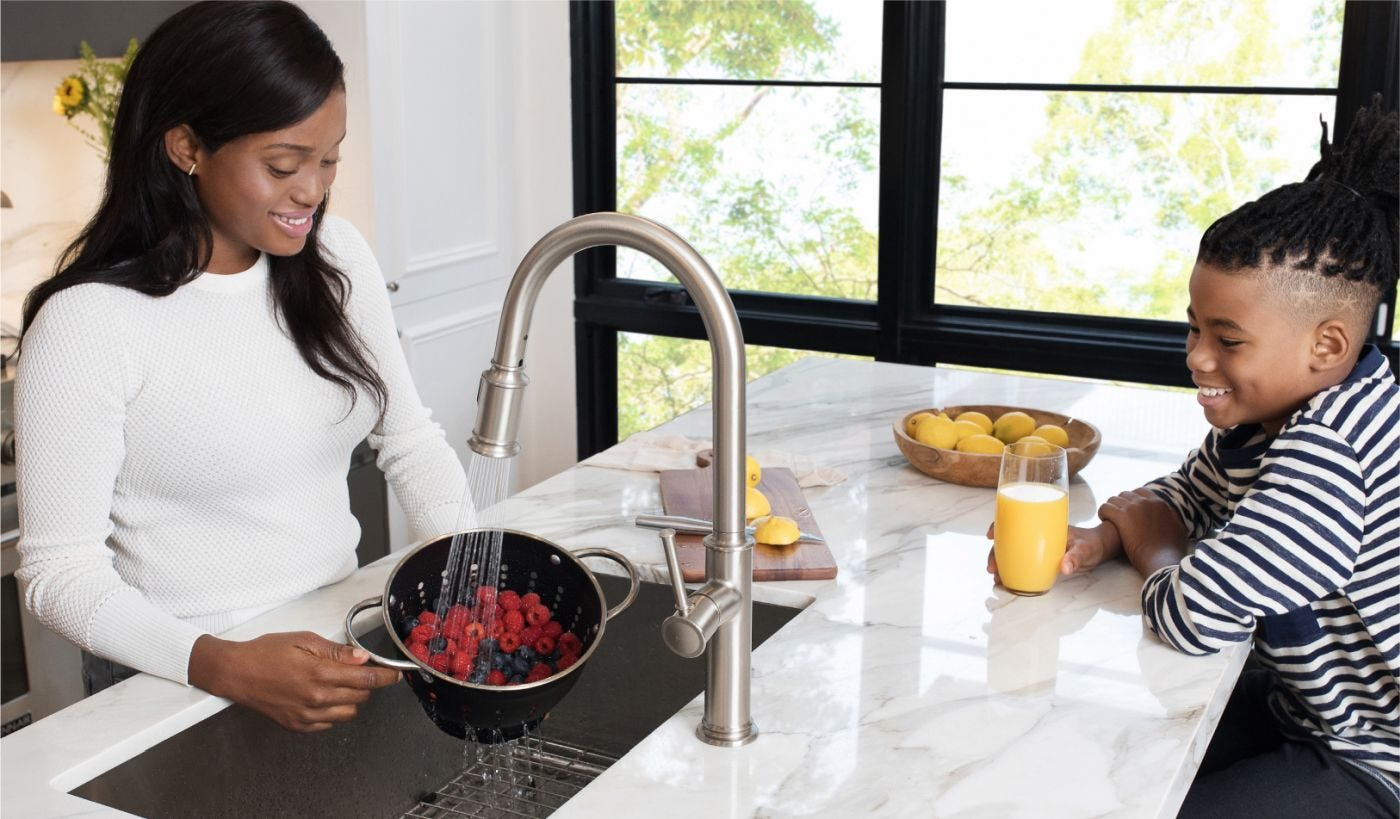 boy with mother over kitchen counter looking at faucet spraying fruits with water